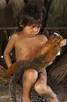Huaorani Indian child holding hunted Dusky Titi Monkey (Callicebus moloch). Gabaro Community, Yasuni National Park, Amazon rainforest, Ecuador, South America.