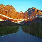 Midnight sun at peak Stjerntind, under road, Lofoten, Northern Norway