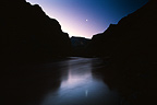 A crescent moon hangs in the sky after sunset over the Colorado River in Grand Canyon National Park.