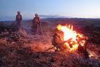Two members of the Wolf Creek Hotshot Crew warm up next to a burning Juniper stump the morning after a long night shift, New Mexico