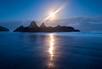 A streak of light cuts through the full moon over the rock formation, Seal Rocks State Park, Oregon, USA
