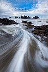 Water rushes through the legs of the photographer and back to sea, Seal Rocks State Park, Oregon, USA
