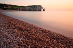 Limestone cliffs of Etretat and pebble beach at sunset