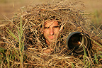 Animal photographer stalking under dry grass