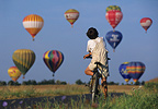 Young cyclist watching hot air-ballons taking�off Lorraine